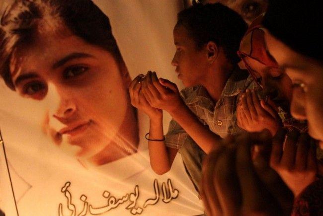 Pakistanische Kinder beten für die angeschossene Kinderaktivistin Malala Yousafzai.