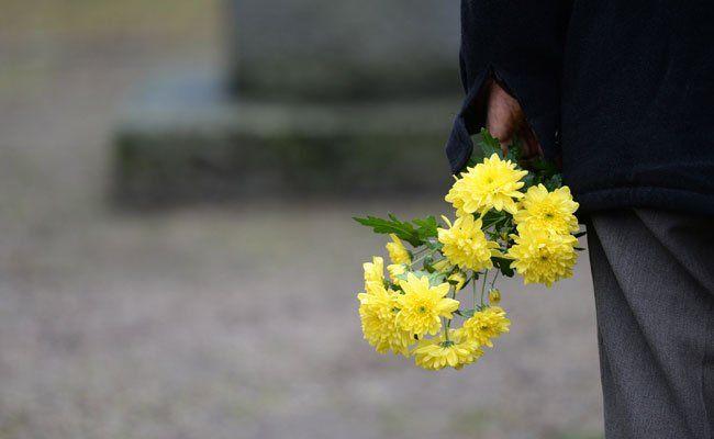 Mit einem Strauß Blumen gedenkt ein Mann den Opfern des NS-Regimes.