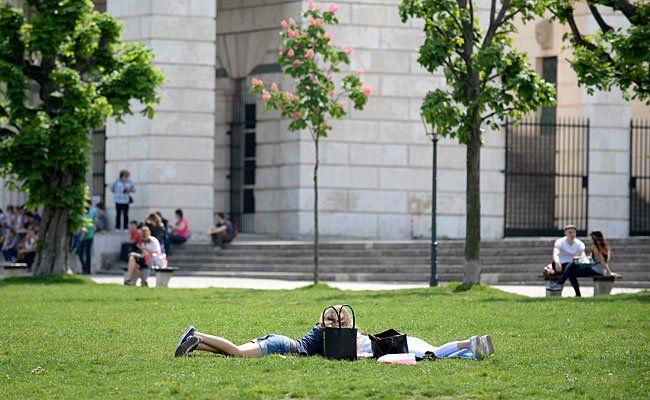 Menschen genießen am Dienstag die sommerlichen Temperaturen bis 28 Grad auf einer Wiese am Heldenplatz in Wien
