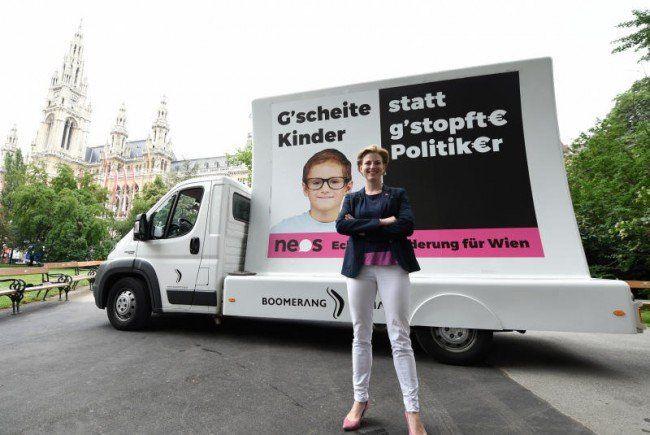 Spitzenkandidatin Beate Meinl-Reisinger zeigt die neue NEOS-Kampagne.