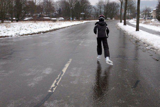 Ein Mann läuft mit Schlittschuhen auf einer durch Blitzeis gefrorenen Straße.