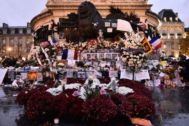Blumen, Kerzen und Nachrichten nach dem Terror in Paris am Place de la Republique.