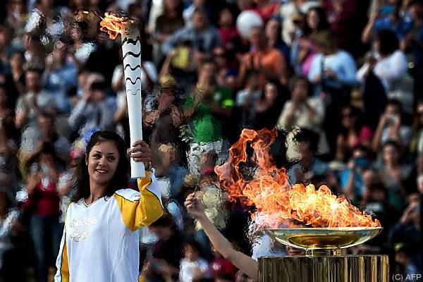 Griechische Ruderin Katerina Nikolaidou mit der olympischen Fackel