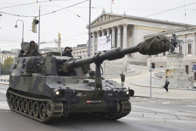 Panzer und Kettenfahrzeuge fahren vor.