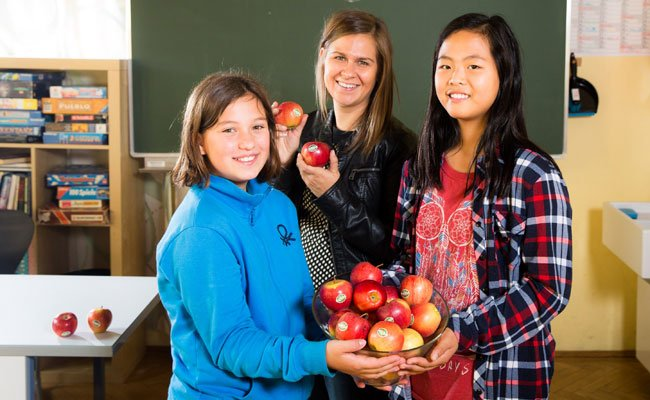 Timna und Yoojin vom Döblinger Gymnasium freuen sich mit Ernährungswissenschafterin Mag. Karin Blagusz (SIPCAN) über die Bio-Äpfel von SPAR Natur*pur