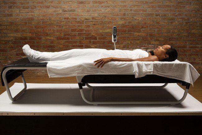 """Eine Frau bei der Entspannung auf einer """"Ohmm""""-Massageliege."""