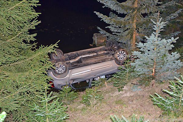 Unfallfahrzeug auf dem Dach in Teich gelandet
