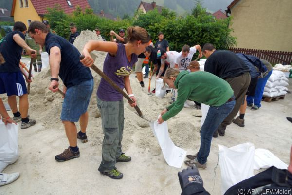 Freiwillige Helfer füllen Sandsäcke
