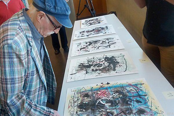 Künstler Staudacher betrachtet die gefälschten Werke