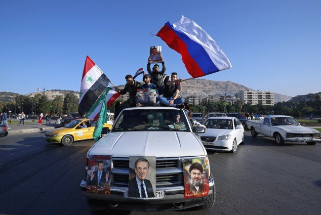 Unterstützer dersyrischen Regierung fahren durch Damaskus.