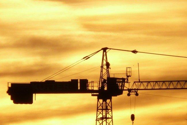 Die Männer kletterten auf den Baukran, um den Sonnenuntergang über Wien zu sehen.